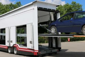 A city car in loading position on the loading ramp of a Confidential SHR, enclosed Lohr car-carrier;