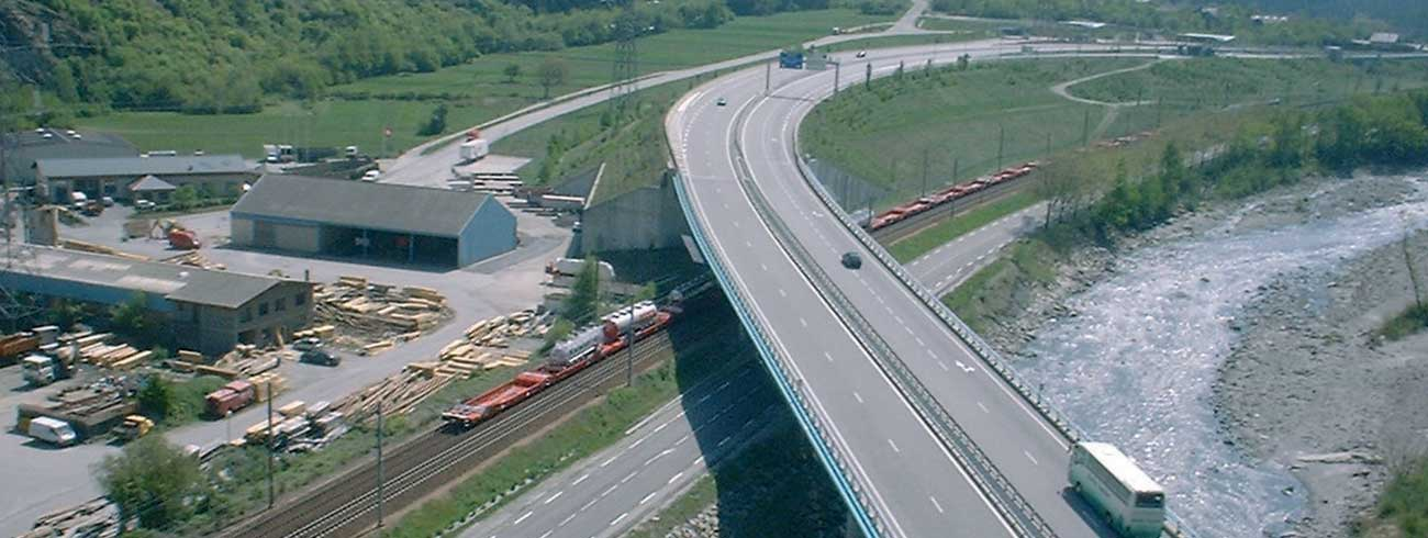 A train composed by Lohr UIC Wagon moving under a bridge with an highway.