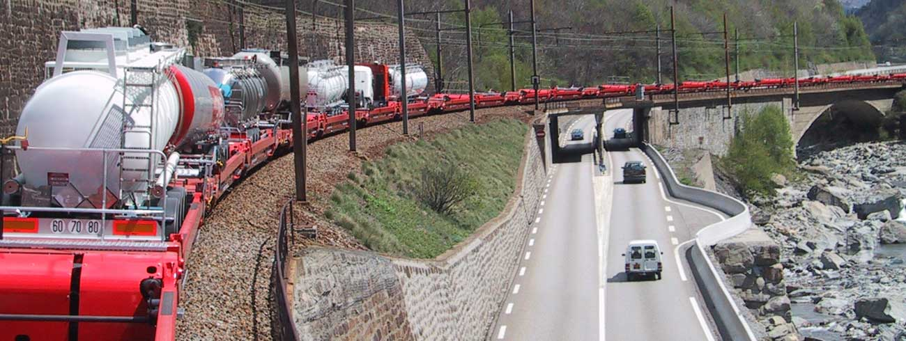 A train composed by Lohr UIC Wagons moving next to a road with cars.
