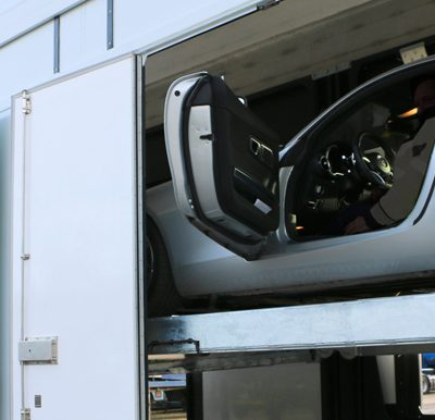 a Luxurious car loaded in a Confidential SHR, both have open doors.