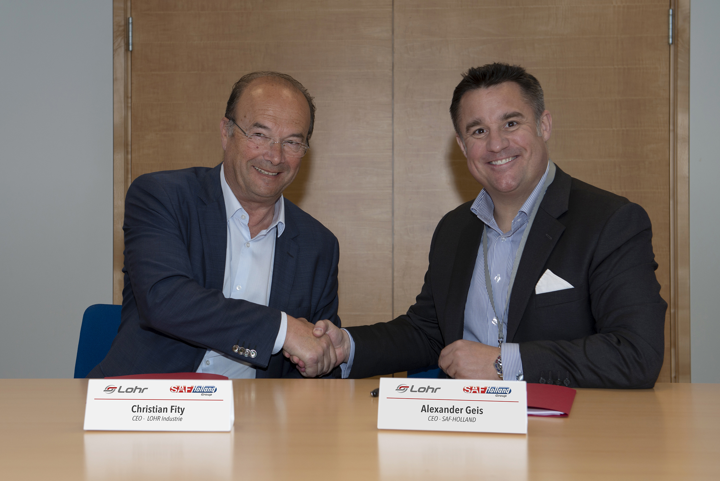 The Managing Directors of the Lohr Group and SAF Holland shake hands after signing a partnership.